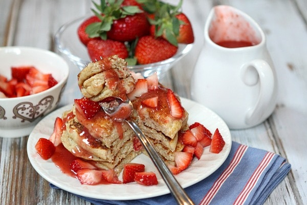 stack of strawberry ricotta pancakes with a fork taking a bite of them. lots of fresh strawberries and strawberry sauce on top with fresh strawberries and pitcher of sauce in background.