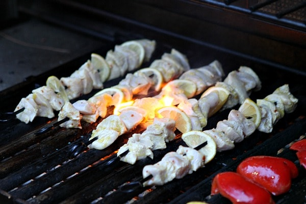 rosemary lemon chicken skewers on the grill with fire
