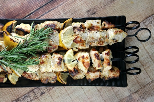 Rosemary lemon chicken skewers on a black tray with fresh lemon and fresh rosemary garnish