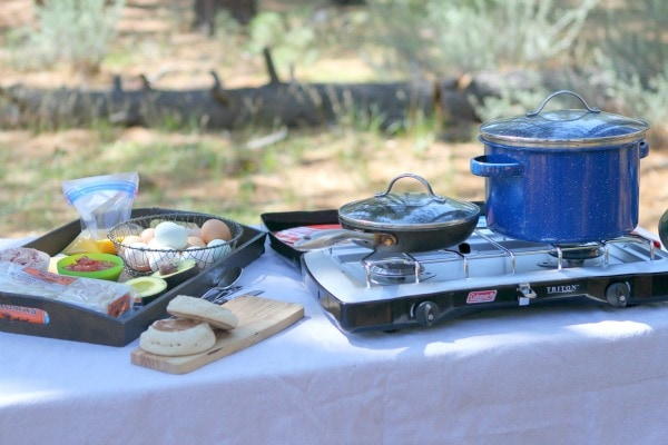 Set up at a campground for making Camping Breakfast Sandwiches. camp stove with blue pot and skillet on top. tray with ingredients for the sandwiches on top. english muffins on a cutting board.
