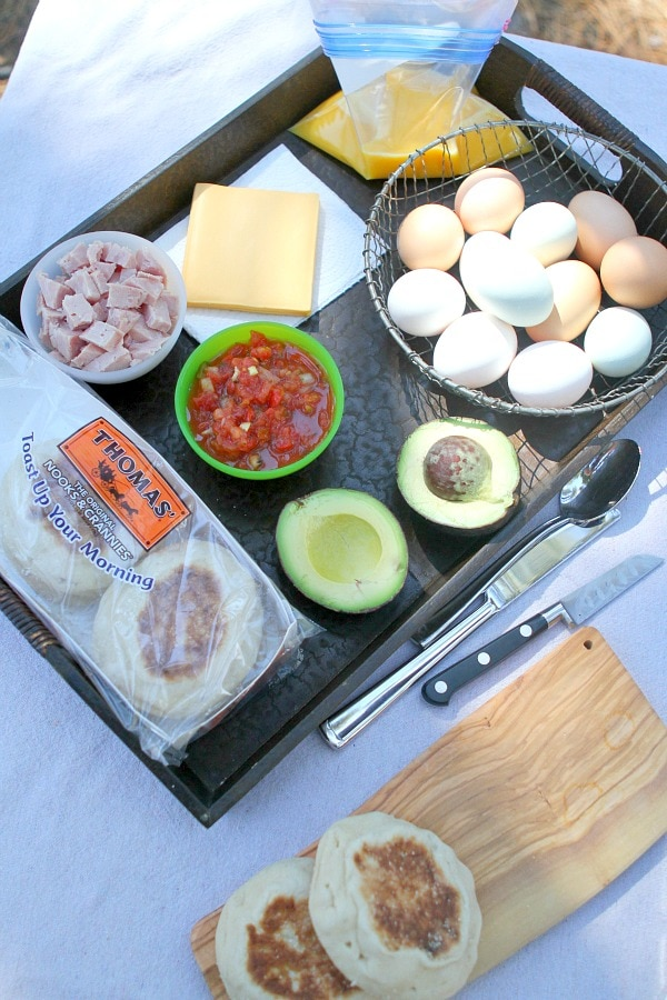 Ingredients displayed for Camping Breakfast Sandwiches: English muffins, avocado, salsa, ham, cheese, scrambled eggs in a plastic bag and eggs in a basket. Utensils and a cutting board on the side.