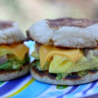 two camping breakfast sandwiches sitting side by side on a blue striped tablecloth
