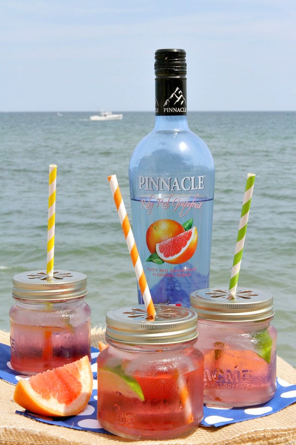 three ruby sunset cocktails in jars with straws and fresh grapefruit with a bottle of grapefruit vodka and the ocean in the background