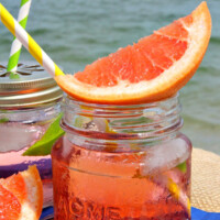 ruby sunset cocktail in a small glass jar garnished with fresh grapefruit, another cocktail next to it. Sitting on a blue napkin with white polka dots with the ocean in the background