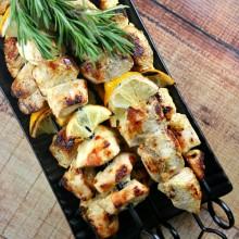 Rosemary lemon chicken skewers on a black tray with fresh lemon and fresh rosemary garnish