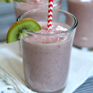 Kiwi Strawberry Smoothies in glasses garnished with a kiwi wedge and red/white straws
