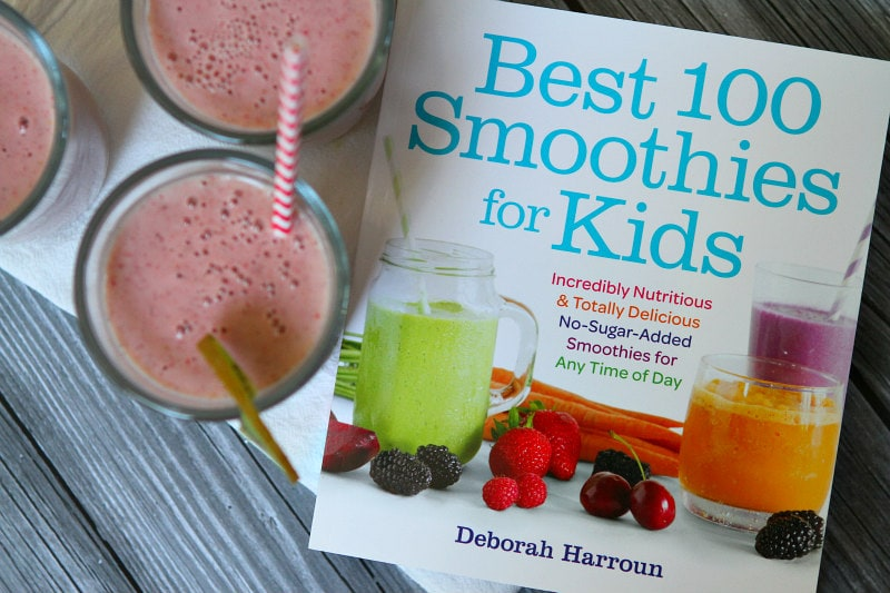 Best 100 Smoothies for Kids cookbook cover with overhead shot of three strawberry kiwi smoothies with straws