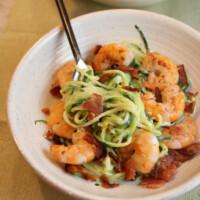 white bowl with fork of alfredo zoodles and shrimp