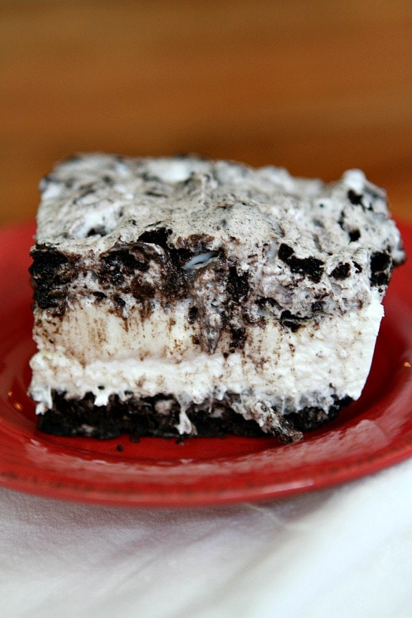 slice of no bake oreo cheesecake bar on a red plate on top of a striped white cloth napkin