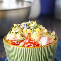 Summer Macaroni Salad in a green bowl sitting on a blue cloth napkin with a stainless steel bowl in the background
