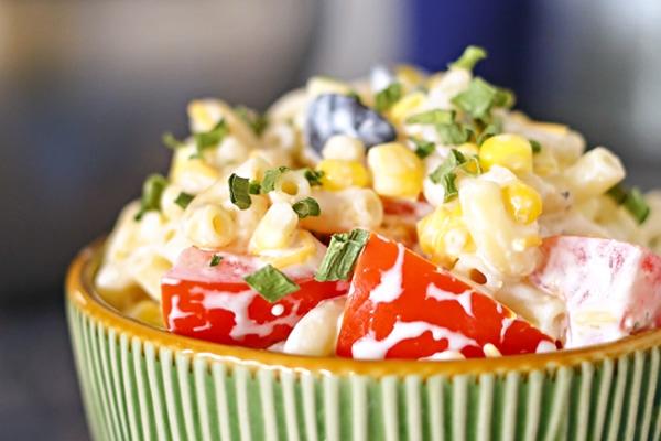 close up shot of summer macaroni salad in a green bowl