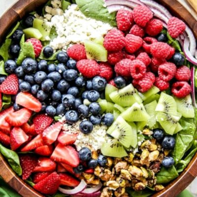 Overhead shot of kiwi berry salad in a wooden salad bowl with a green cloth napkin on the side