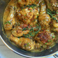 chicken pieces cooking in pan with sauce and fresh thyme