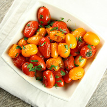 overhead shot of sauteed tomatoes with thyme in a white bowl garnished with fresh parsley sitting on a white cloth napkin