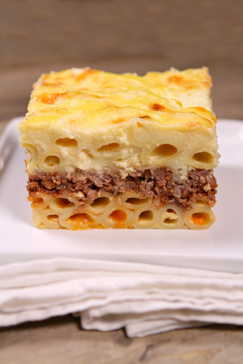 slice of pastitsio sitting on a white plate on a white napkin