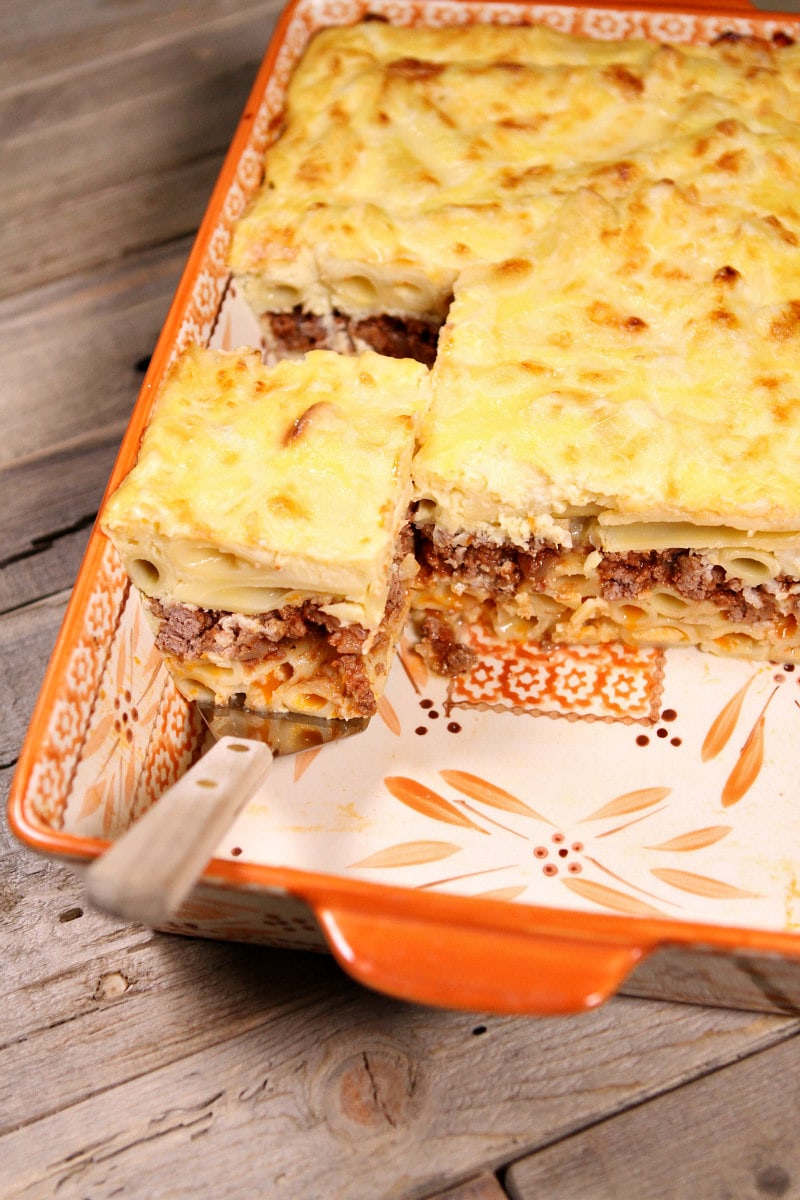 overhead shot of pastitsio in a casserole dish using a spatula to take out a slice