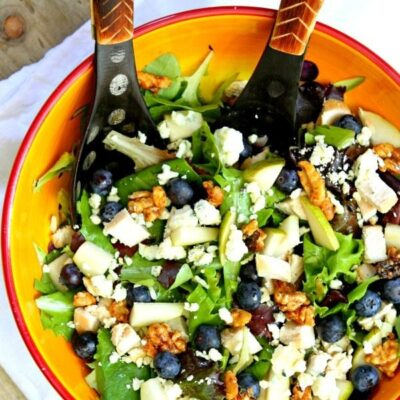 blueberry, blue cheese and glazed walnut salad in a yellow bowl with salad servers