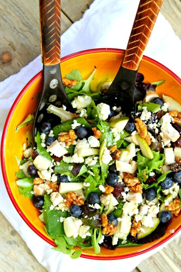 Blueberry, Blue Cheese and Glazed Walnut Salad in a yellow salad bowl with wooden salad servers, sitting on a white towel on a wooden table