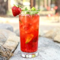 strawberry mojito in a tall glass garnished with a fresh strawberry sitting on rocks in a backyard setting