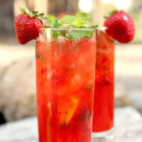 two strawberry mojitos in tall glasses garnished with fresh strawberries sitting on a rock in the backyard