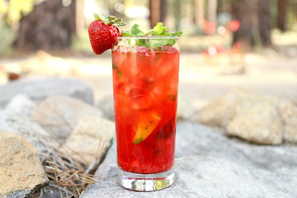 Strawberry Mojito in a tall glass garnished with a fresh strawberry set on rocks in a backyard setting