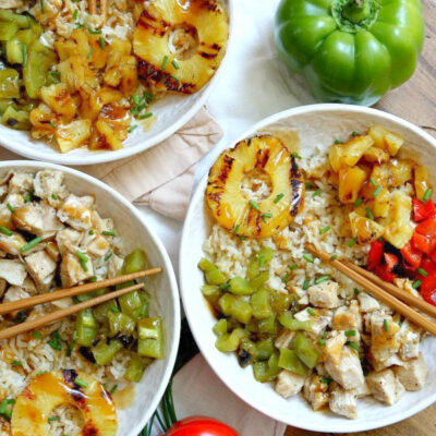 overhead shot of 3 white bowls filled with grilled chicken and pineapple rice bowls with chopsticks. Set on a white napkin with a wood board background with fresh bell peppers and green onions garnish.
