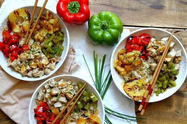 overhead shot of 3Grilled Chicken and Pineapple Rice Bowls with Teriyaki Glaze in white bowls with chopsticks. bell peppers and chives displayed for garnish