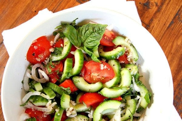 Overhead shot of Tomato Cucumber and Basil Salad in a white bowl with a white napkin on a wood surface
