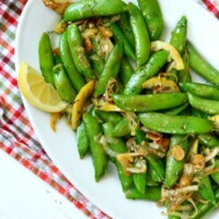 lemony stir fried sugar snap peas on a white serving platter set on a checked cloth napkin