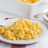 macaroni and cheese on a white plate set on a red and white plaid napkin with white casserole dish of macaroni and cheese in the background