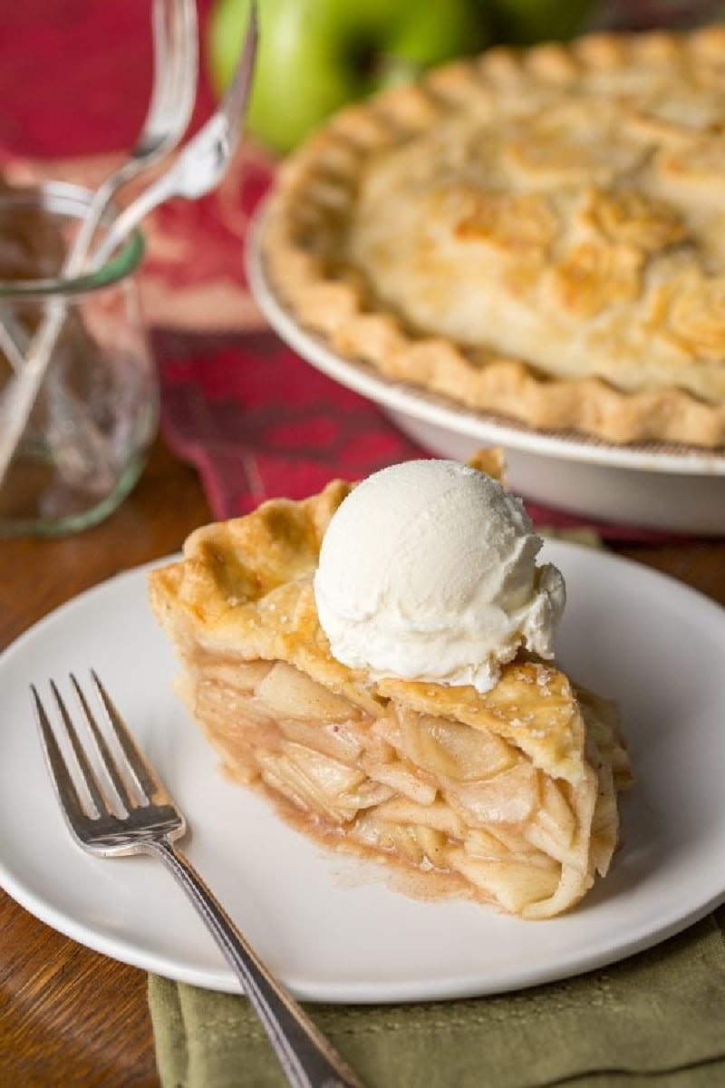 slice of apple pie on a plate with rest of pie in background