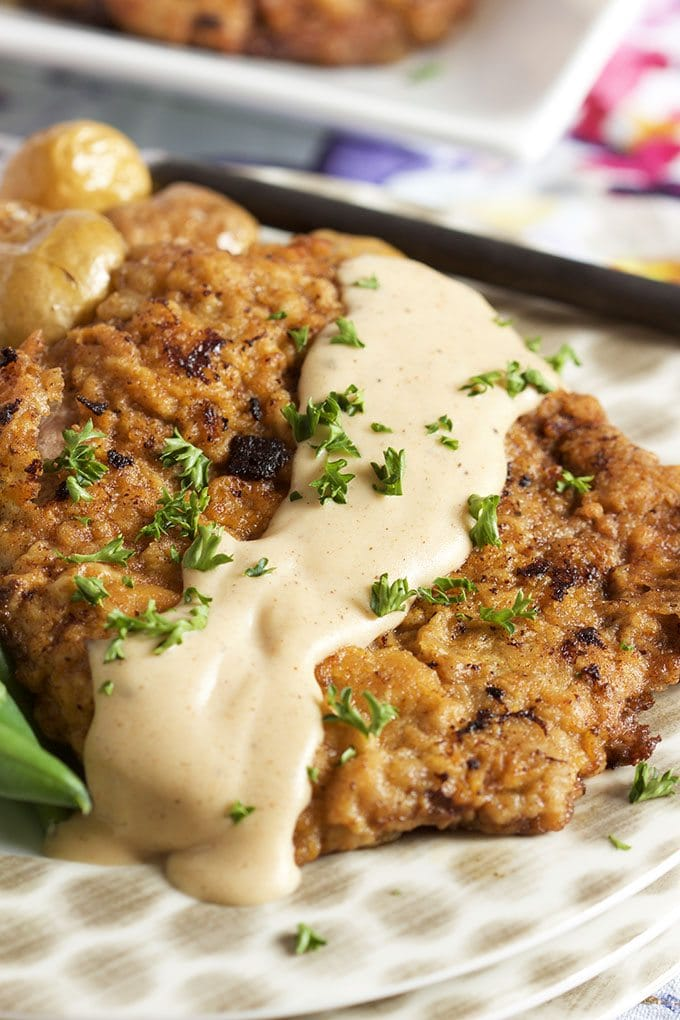 Chicken Fried Steak topped with gravy displayed on a polka dot plate