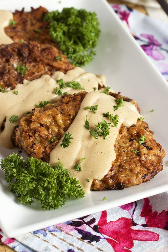 chicken fried steak topped with gravy and fresh parsley