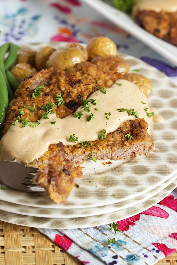 Chicken Fried Steak displayed on a stack of polka dot plates topped with gravy