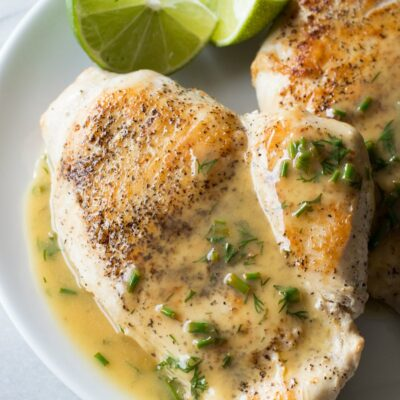 chicken topped with lime butter on a white plate with fresh lime wedges