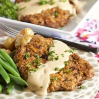 chicken fried steak with gravy on top and fresh green beans. Displayed on a polka dot stack of plates.