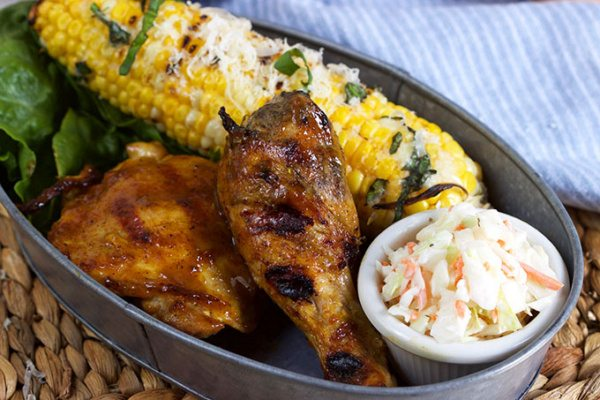 Carolina Style Barbecue Chicken in a metal serving dish with corn on the cob and cole slaw on a woven mat with a white/blue striped napkin on the side