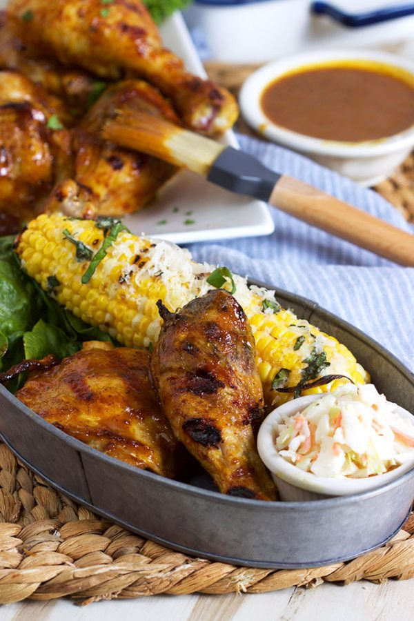 Carolina Style Barbecue Chicken in a metal serving dish with corn on the cob and cole slaw with more chicken and sauce and a brush in the background