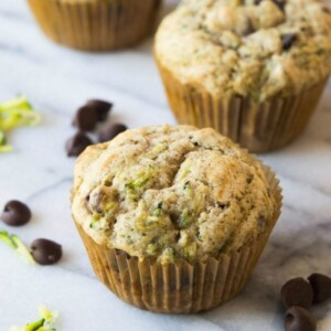 zucchini chocolate chip muffins sitting on a marble surface with chocolate chips and shredded zucchini scattered about