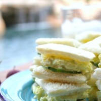 avocado egg salad tea sandwiches stacked on a blue plate on a red/white checked tablecloth with pool backyard setting