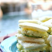 avocado egg salad tea sandwiches stacked on a blue plate with a checked tablecloth underneath. pool in the background.