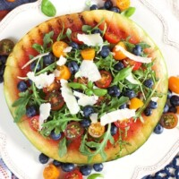 Grilled Watermelon Pizza with Blueberries, Parmesan and Arugula on a white plate with more tomatoes and fruit and a wedge of parmesan in the background