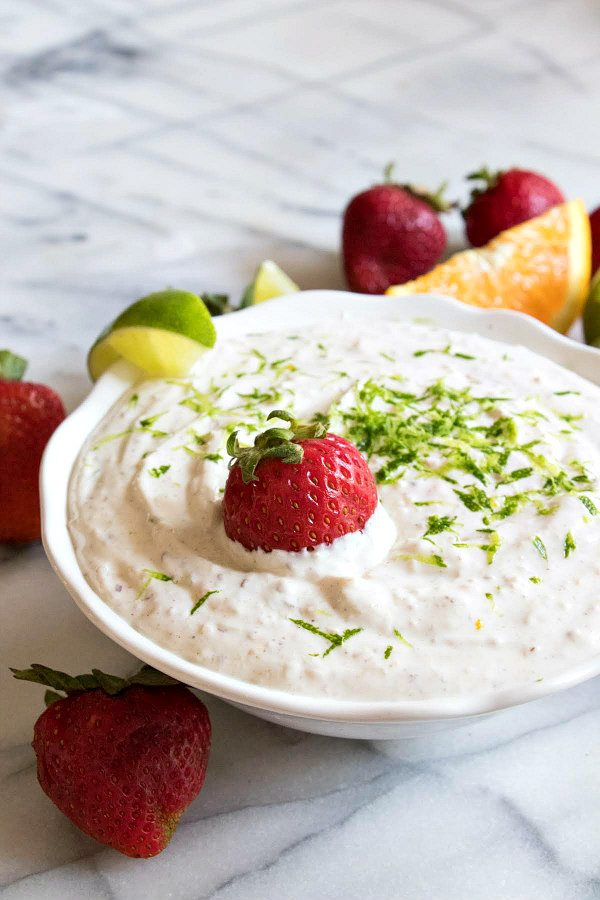 margarita fruit dip garnished with strawberries and lime, displayed in a white bowl on a marble surface