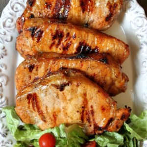 apple and blue cheese stuffed grilled pork chops on a white serving platter with lettuce and tomato salad