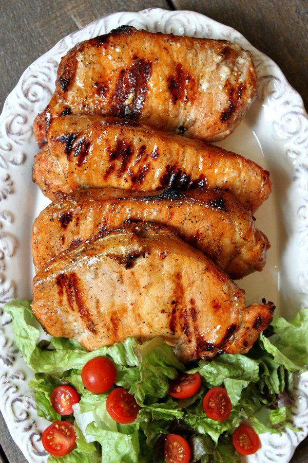 Blue Cheese and Apple Stuffed Grilled Pork Chops displayed on a white platter with a lettuce and tomato salad