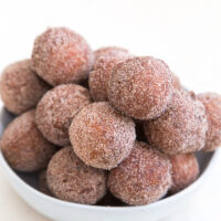 apple cider doughnut holes stacked in a white bowl