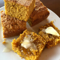 pumpkin cornbread on a white plate sliced with butter