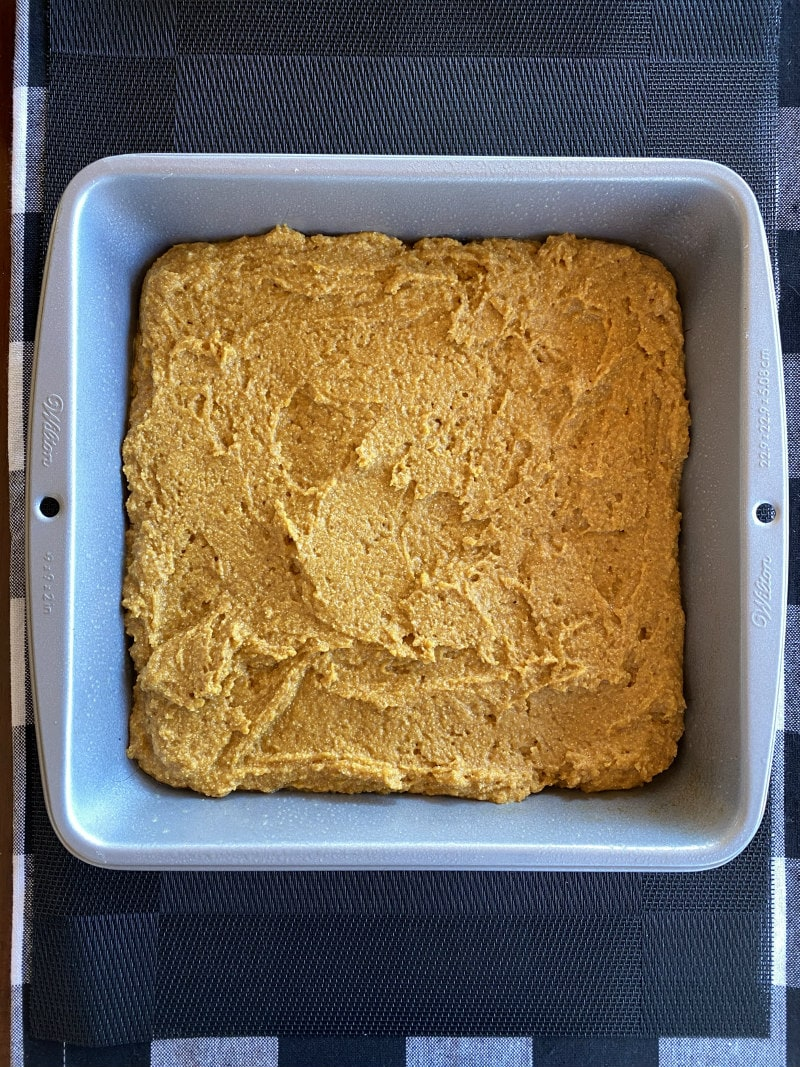 pumpkin cornbread in a baking pan ready for oven