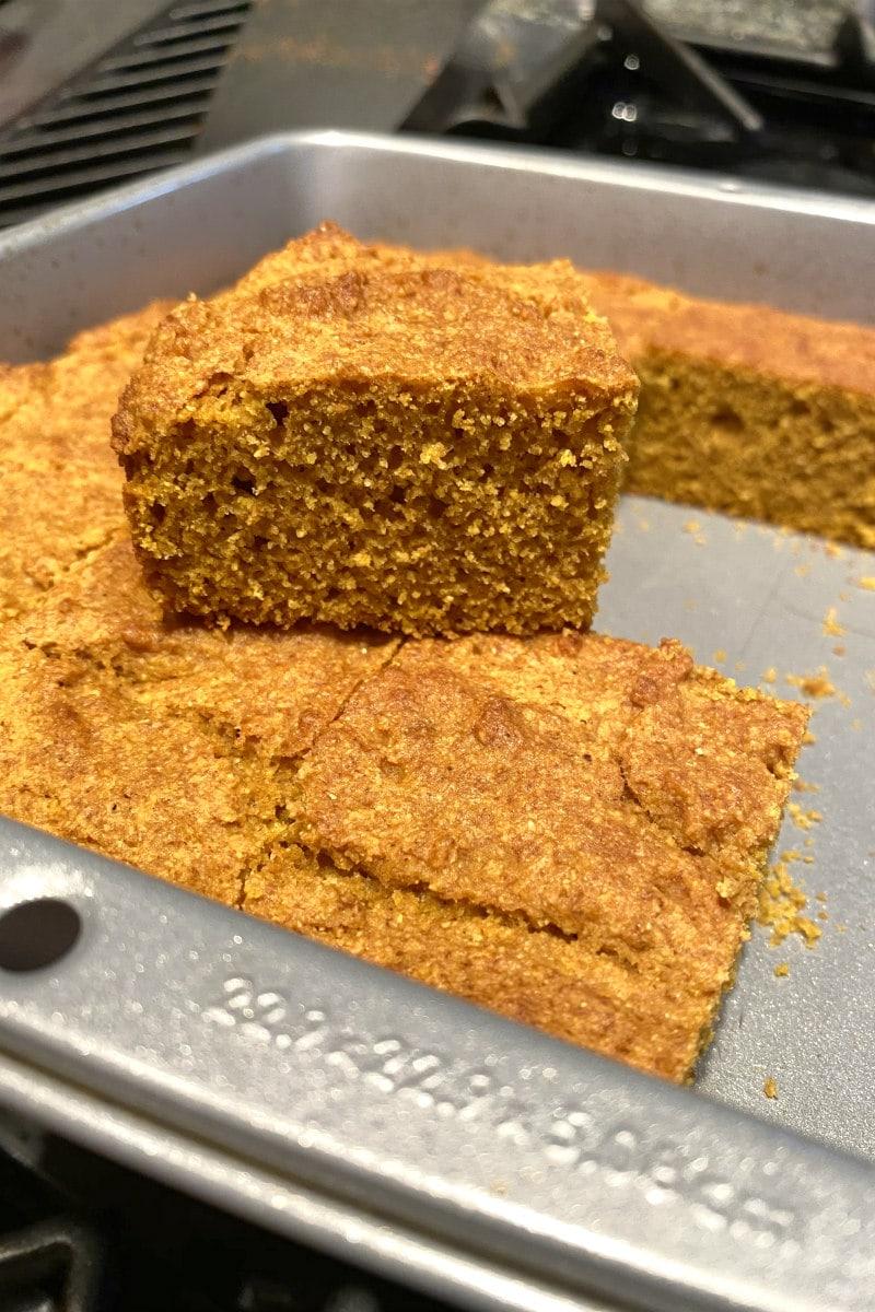 pumpkin cornbread in a baking pan with slice on top