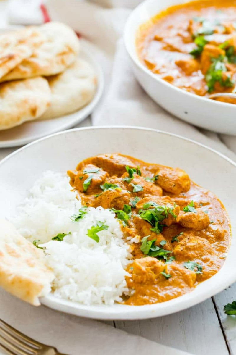 servings of indian butter chicken in white bowls with white rice with pita bread in the background